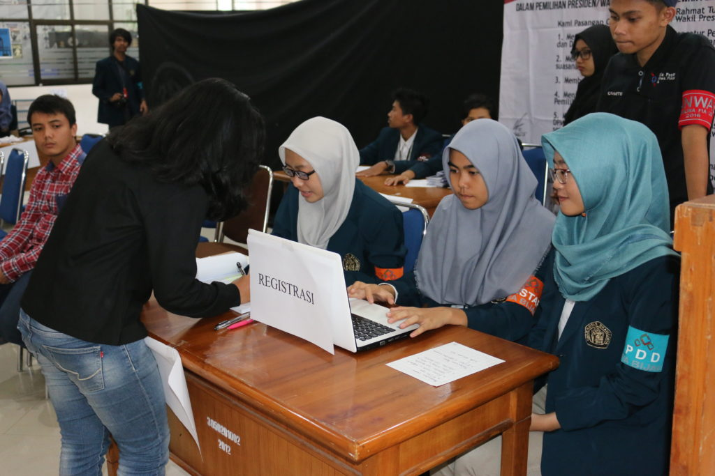 Panitia Pemira FIA UB 2016 membantu registrasi salah satu pemilih