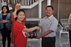 Pembantu Dekan I FIA UB, Dr. M.R. Khairul Muluk, memberikan cinderamata kepada Ms. Lynn Zhou (Singapore Polytechnic)